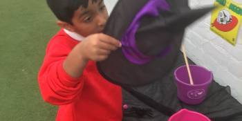 This child investigated the role play area outside and enjoyed making potions in the cauldron and looking at the witches hat.